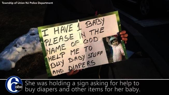女子手持字牌及幼兒照片,聲稱自己需要錢購買嬰兒產品。(ABC電視台截圖)