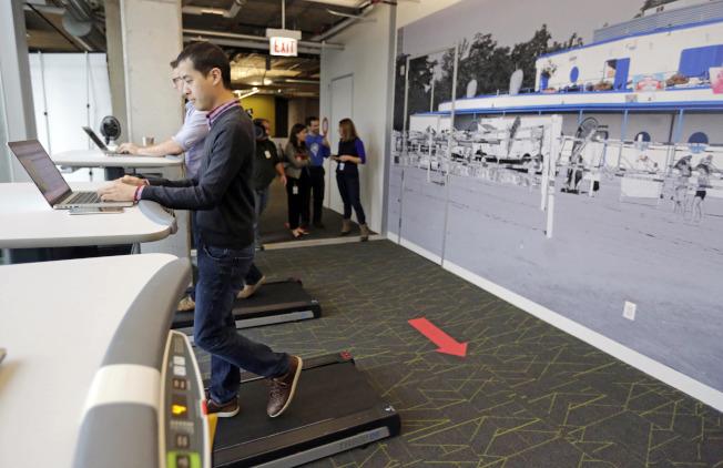 谷歌芝加哥總部的員工,在附設桌面跑步機上,一邊工作、一邊運動。(美聯社)