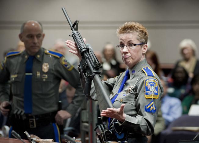 康州最高法院14日裁定槍枝製造商需對珊迪虎克小學屠殺案負起法律責任。圖為一名康州州警2013年展示AR-15步槍。(美聯社)