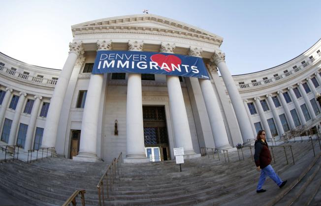 聯邦移民當局開始規避移民庇護城市,悄悄與當地警方合作。圖為丹佛市政大樓懸掛著「我們愛移民」的橫幅。(美聯社)
