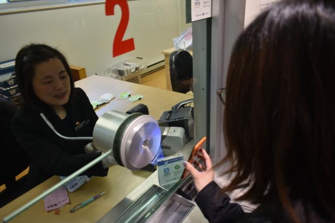 一名中國公民在中領館2號收費窗口,透過刷二維碼的方式微信支付領事證件費用。(記者黃少華╱攝影)
