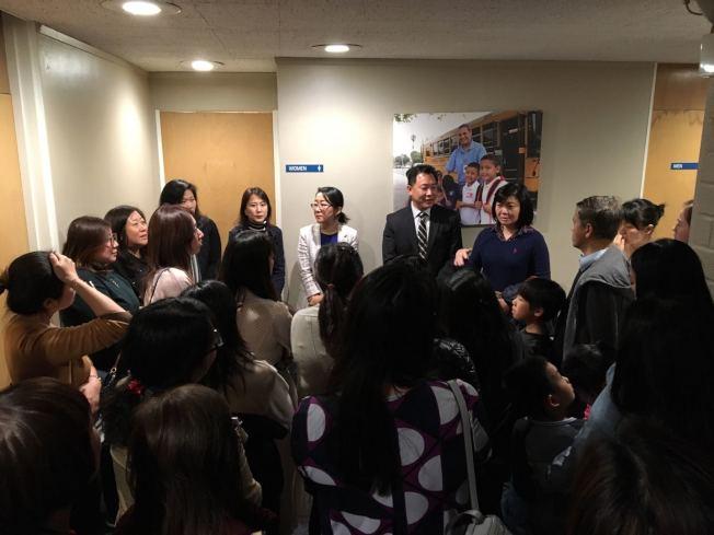 眾多家長聚集在教委會例會場所外面的走廊,聽學區中學高中課程華裔負責人張忠直(右四)對學區實施學生性教育課程的解釋。(記者啟鉻/攝影)