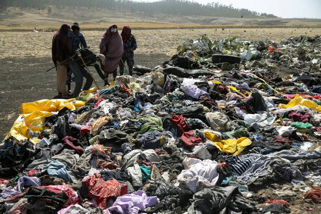 衣索比亞警方12日在飛機失事現場搜尋旅客隨身物品。(路透)