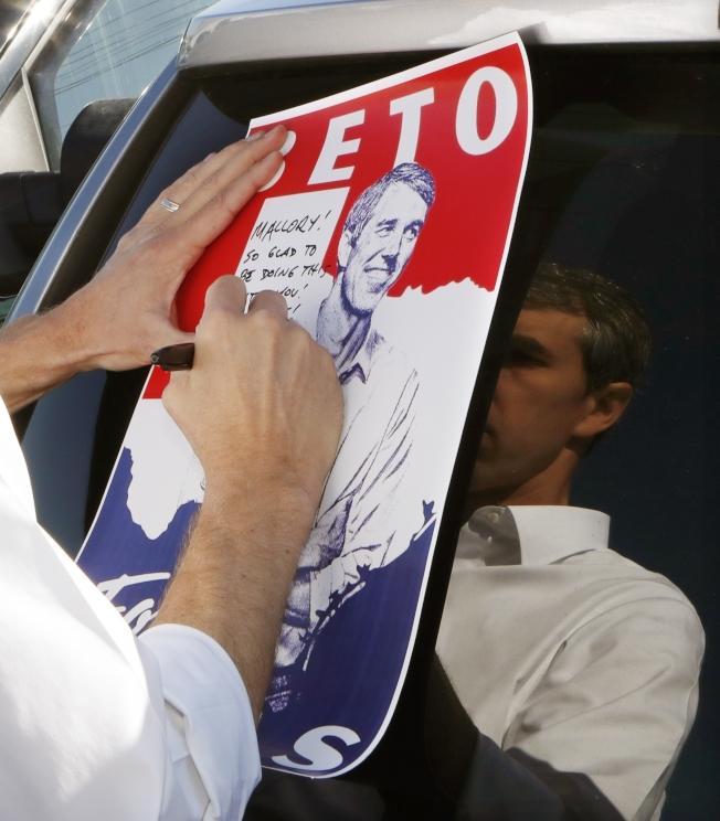 前德州國會議員歐洛克宣布參選後,所到之處造成旋風。圖為歐洛克18日在密西根州拜票為支持者在海報上簽名。(美聯社)