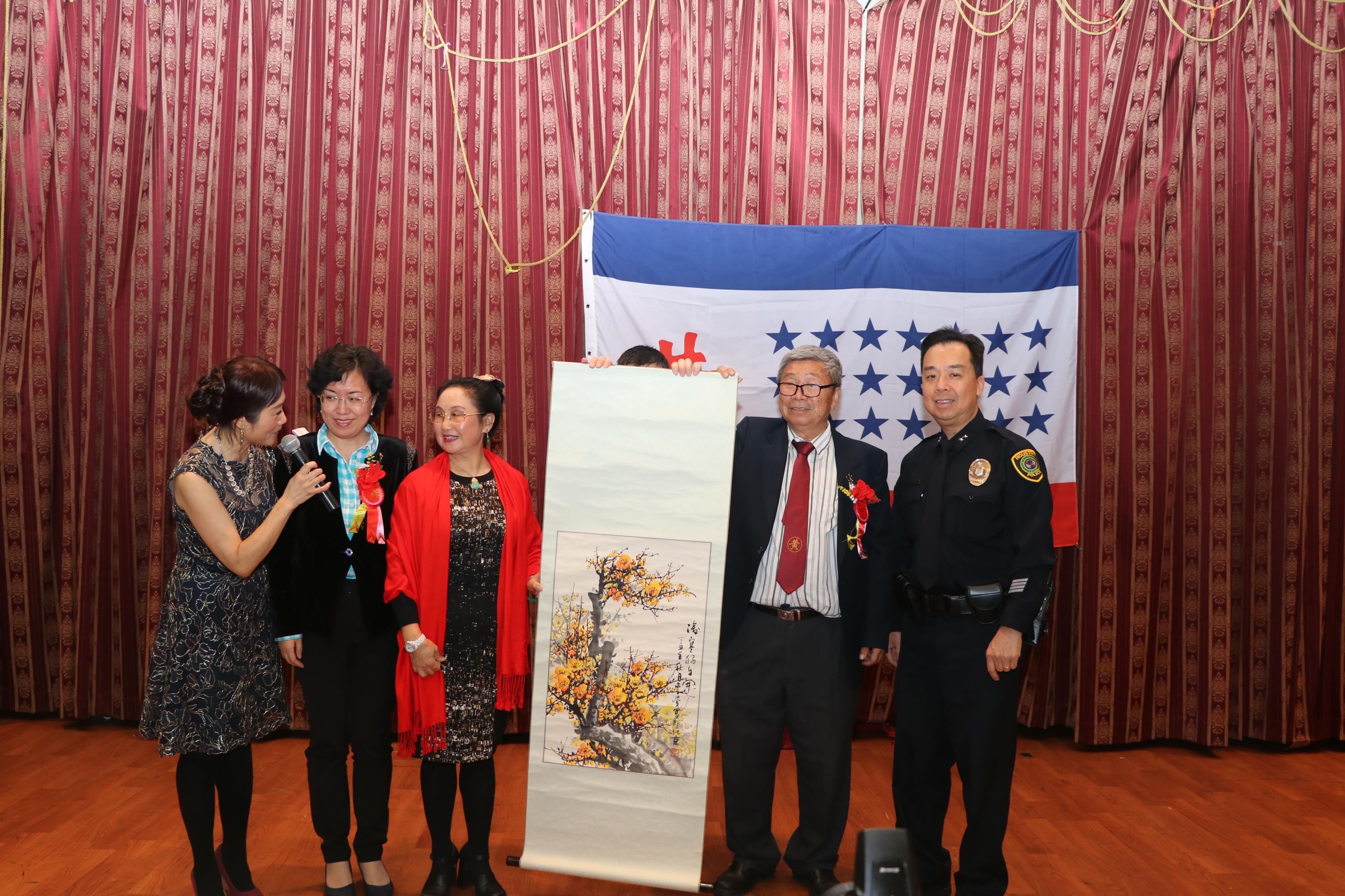 來自合肥的畫家李曼(左三)捐出畫作「寒梅花開」給大會主席黃孔威(右二)。左二為中國駐休士頓副總領事劉紅梅,右一為HPD副警長Henry Gaw。