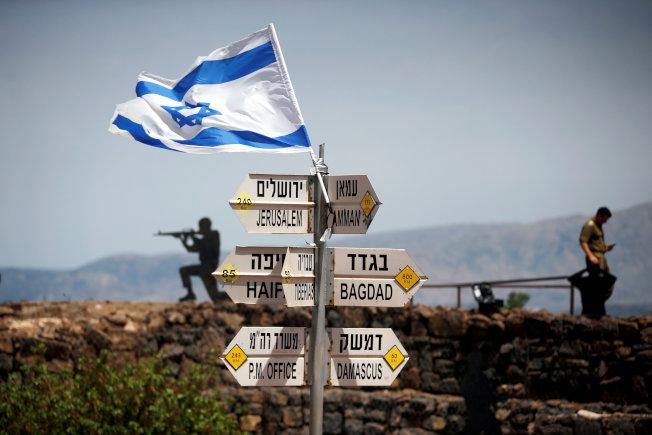 以色列占領的戈蘭高地豎立許多路標,以色列士兵在旁警戒瞭望。(路透)
