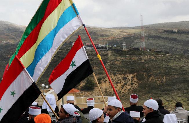 戈蘭高地德魯茲族居民望著敘利亞,揮舞著敘利亞國旗和德魯茲旗幟。(路透)