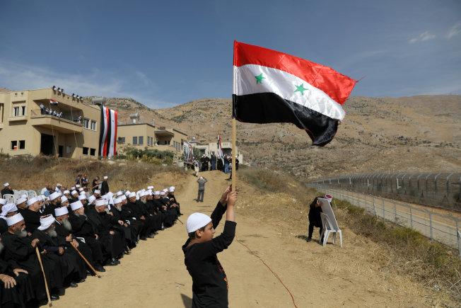 戈蘭高地德魯茲族居民望著敘利亞,揮舞敘利亞國旗。(路透)