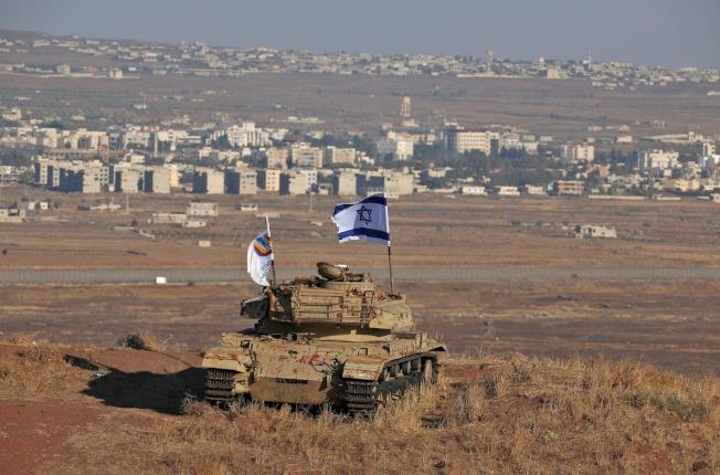以色列坦克居高臨下,從戈蘭高地望著前方的敘利亞村落。(Getty Images)