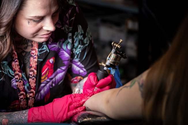 紋身師用針刺穿皮膚,針頭將墨滴注入皮內。(Getty Images)