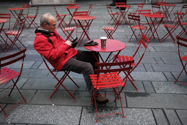 人們對智慧手機的依賴程度愈來愈高,但對手機可能偷聽或監控使用者的疑慮也增加。圖為紐約一名男子一面享用咖啡,一面玩手機。(Getty Images)