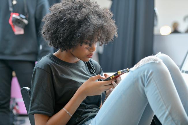 人們對智慧手機的依賴程度愈來愈高,但對手機可能偷聽或監控使用者的疑慮也增加。圖為一名模特兒在今年2月紐約時裝周上,用手機消磨等待化妝師的時間。(Getty Images)