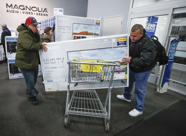 近年電視價格大幅下跌,原因是智慧電視一旦進入家家戶戶,就可以大方取得觀看紀錄,每個觀眾都在幫它賺錢。圖為民眾購買大電視 。( Getty Images)