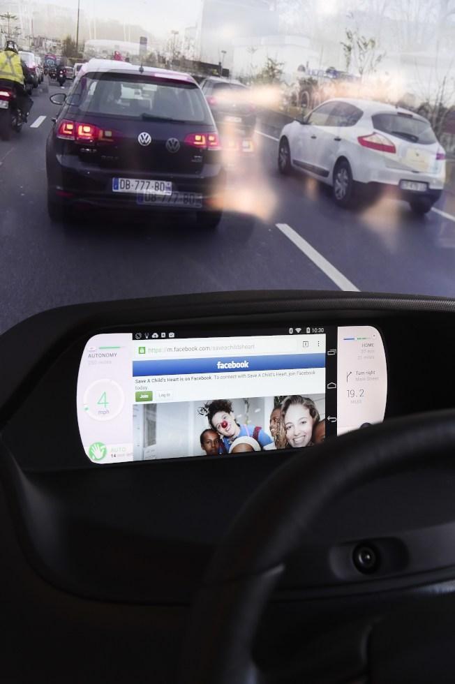 圖為一名駕駛人的行車時,使用車上娛樂系統。(Getty Images)