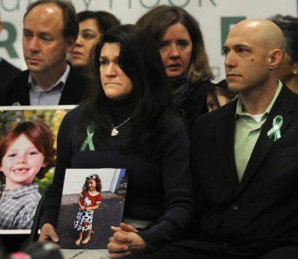 珊迪虎克小學校園槍案受害學生艾薇兒的父親里奇曼(右)自殺,圖為他和妻子手持女兒的照片。(美聯社)