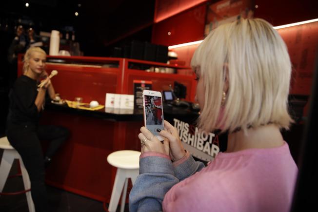 服裝設計師維多利亞‧海德(Vittoria Hyde,右)在餐廳幫時尚部落客克利薩伊‧印科維耶(Clizia Incorvaia)拍網美照。(美聯社)