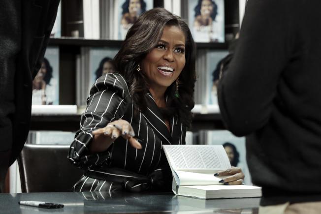前第一夫人米雪兒‧歐巴馬的《Becoming》(蛻變)即將成為史上最暢銷的回憶錄。圖為去年12月米雪兒在紐約舉行簽名會。(美聯社)