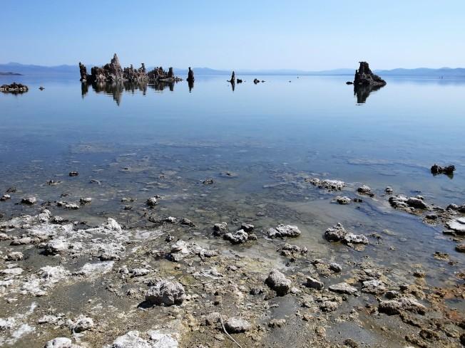 如鏡面一般的湖水照映著這些石灰華,水天一色,也營造出相當奇幻瑰麗的景緻。