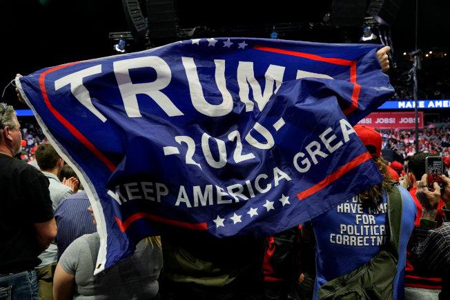 川普在穆勒報告提出後,到密西根州舉行造勢大會。圖為支持者舉起「川普2020」大旗。(路透)