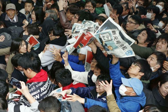 民眾在東京新橋車站瘋搶「新年號」號外。(美聯社)