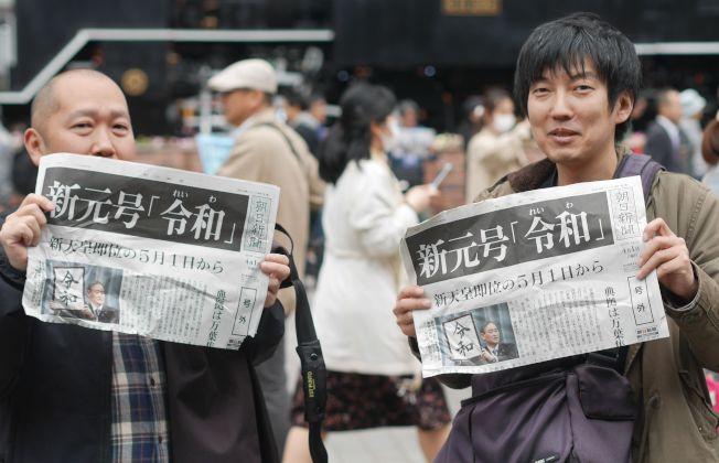 民眾1日在東京街頭拿著日本朝日新聞報導新年號的號外。(Getty Images)