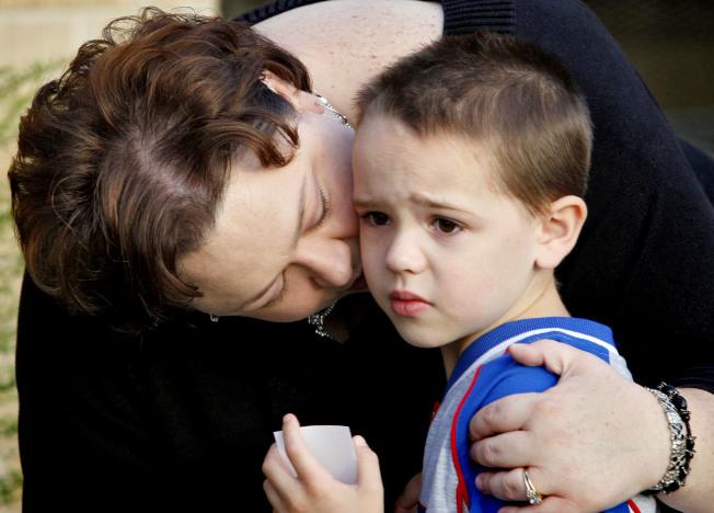 一位母親在兒子上幼稚園首日,親吻孩子臉龐,試圖降低孩子的焦慮感。(美聯社)