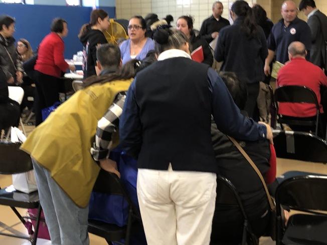 華裔志願者安慰深陷悲痛情緒的老婦。(記者顏潔恩/攝影)