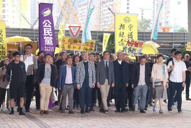 香港「佔中」案10日早上繼續在西九龍法院開庭,法官聆聽部分人求情後,延至4月24日判刑;圖為9名被告(前排)在支持者陪同下步入法庭。(中央社)