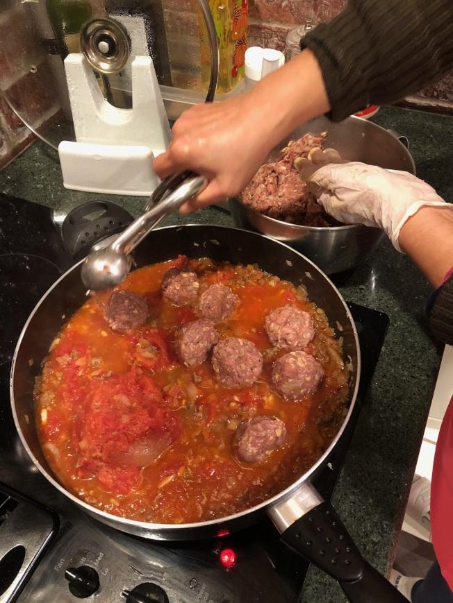 3.放入肉丸,可用挖冰淇淋的勺子做肉丸,另一手同時整形丸子。