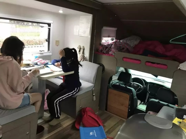 欣欣下課後就在露營車的客廳寫作業,後方就是睡覺的床鋪。(取材自錢江晚報)