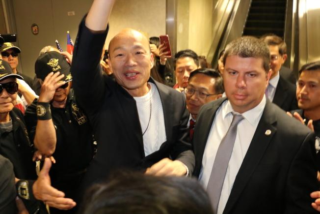 美西時間12日下午4時許,高雄市長韓國瑜從美東城市波士頓抵達西岸城市洛杉磯,現場人潮壅擠,韓國瑜在警察保護下,步出機場上遊覽車回到飯店。(記者王慧瑛/翻攝)