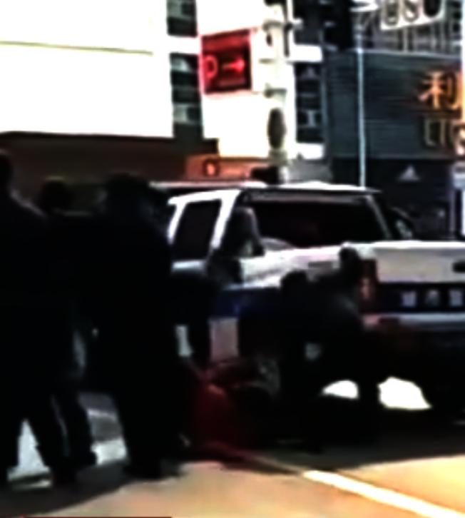 視頻顯示,江蘇城管開車從女子腿上輾壓過去,女子躺在地上呻吟,一旁有大量民眾圍觀。(視頻截圖)