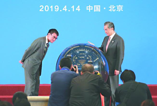 中國國務委員兼外長王毅(右)與日外相河野太郎,14日在北京出席中日青少年交流促進年開幕式 。(美聯社)