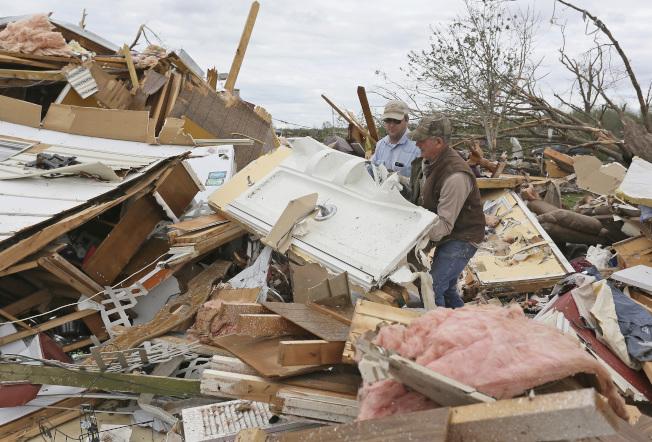 居民在瓦礫中清理家園。(美聯社)