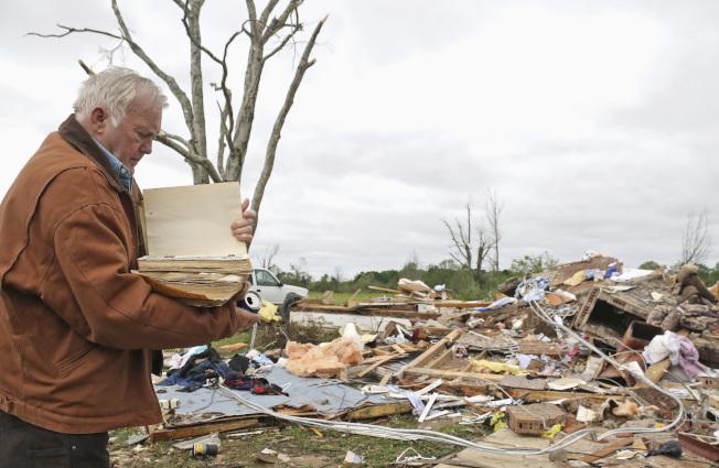 密西西比州漢米爾頓遭龍捲風重創候,一名民居從瓦礫中尋回一本家庭聖經。(美聯社)