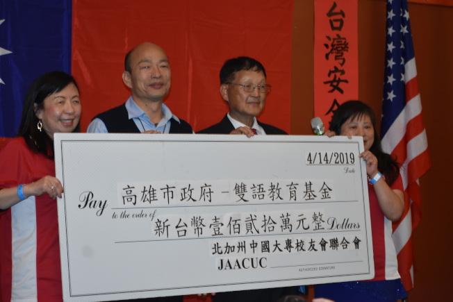 會長朱季光(右二)代表校聯會向韓國瑜(左二)送上120萬元新台幣支票。(記者黃少華/攝影)
