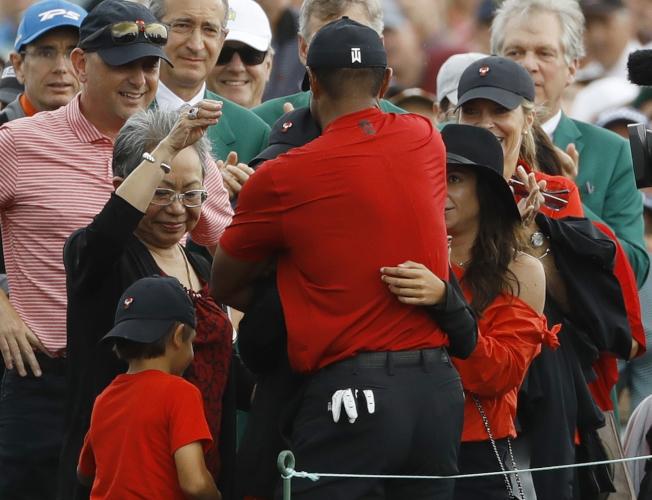 老虎伍茲獲勝後,激動地抱著兒子女兒,母親也在一旁欣慰的流淚。(美聯社)