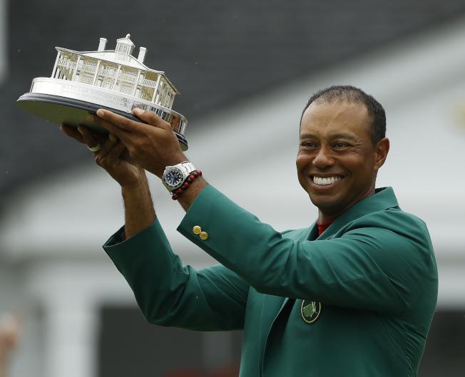 穿上綠色夾克的老虎伍茲高興地舉起獎座。(美聯社)