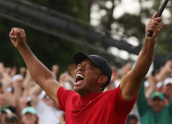 老虎伍茲獲勝後,激動高舉雙手歡呼。(路透)