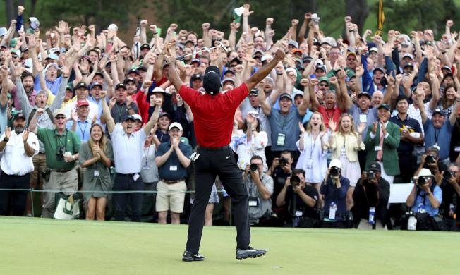 老虎伍茲贏得冠軍後,觀賽的球迷與他一起高舉雙手歡呼,場面令人動容。(美聯社)