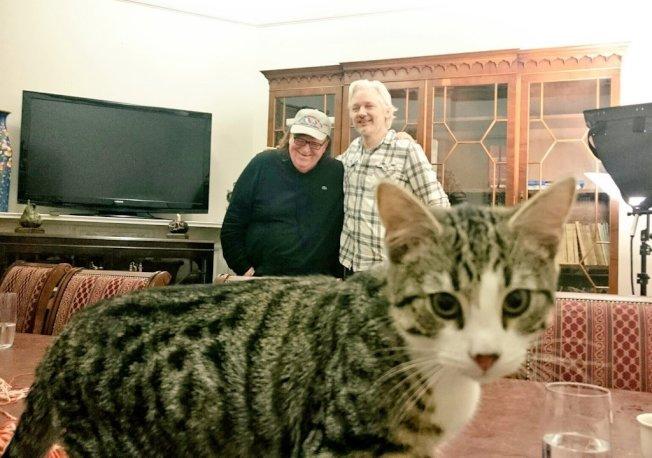 阿桑吉(右)和來訪的美國導演麥可摩爾(左)合照時,貓咪亂入鏡頭。(取材自推特)