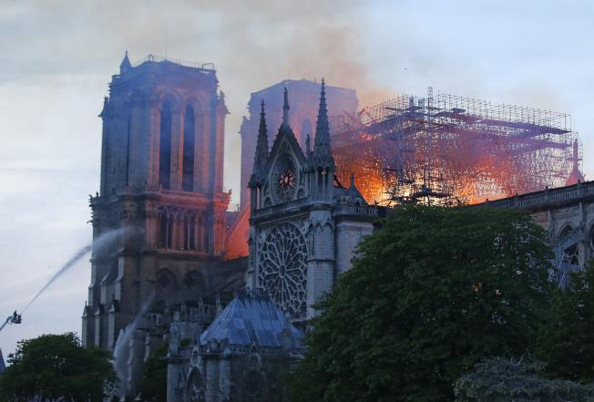 火燒法國巴黎聖母院,濃濃黑煙從建築頂部冒出。(美聯社 )