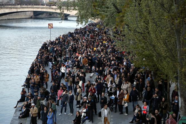 巴黎聖母院起火時,周圍人行道、橋上、河堤邊站滿許多人。(美聯社)