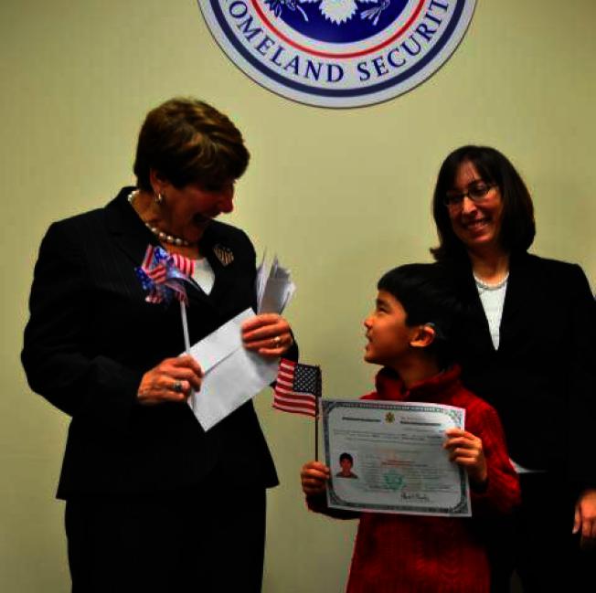 這是移民局官員和一位收養兒童的人士在入籍儀式上合影,而被收養的外國孩子也要申請移民簽證。目前川普政府有意緊縮各種非移民簽證。(國土安全部官網)