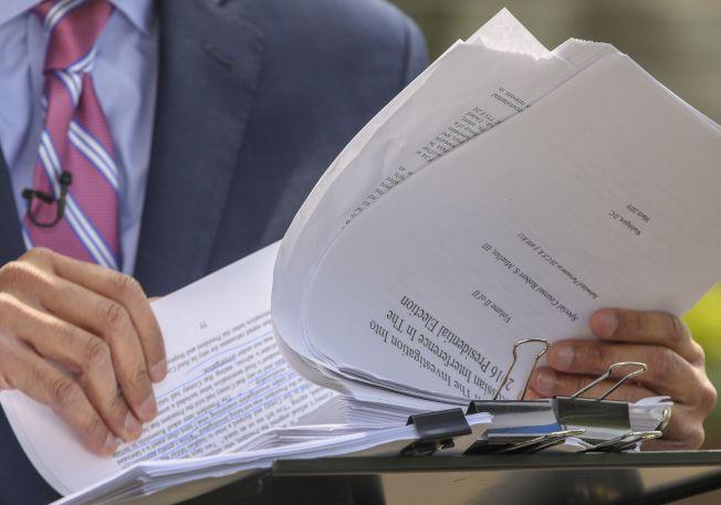 司法部長巴維理公布刪節版穆勒報告,圖為電視記者拿到報告,迫不及待翻閱。(Getty Images)