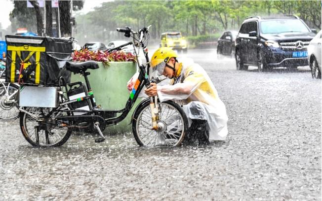 廣東19日遭暴雨冰雹大風夾擊,交通大受影響。圖為一名外送員在雨中修理拋錨的電動車。(中新社)