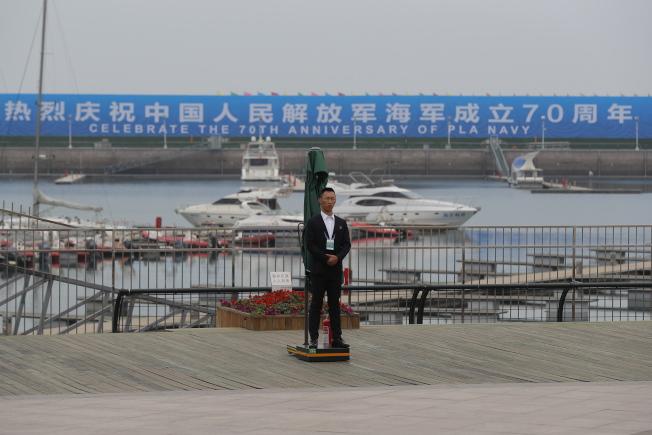 解放軍海軍將在23日舉行建軍70周年一系列海軍活動。圖為工作人員在典禮現場的青島碼頭警戒。(歐新社)