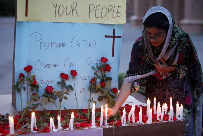 斯里蘭卡連環爆後,一名婦女為遇難者點燭致哀。(美聯社)