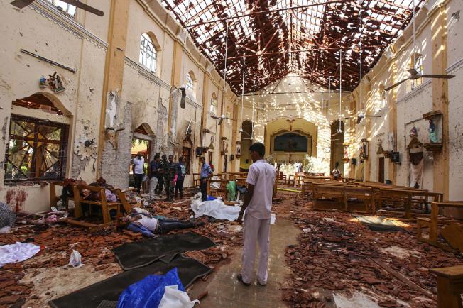 斯里蘭卡可倫坡北郊的聖塞巴斯提安教堂遭炸彈攻擊,屋頂全毀,滿地殘骸,地上還有死難者遺體。(美聯社)