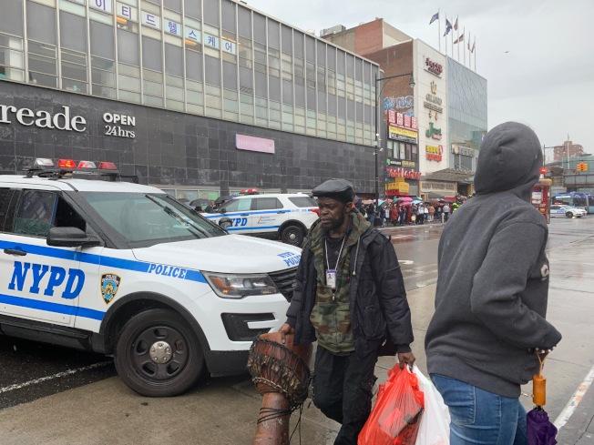 非洲裔車主(戴帽子者)在兩名熱心華裔協助下,在火勢轉大前趕快把貴重物品拿下車。(記者賴蕙榆/攝影)